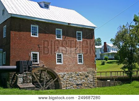 An Old, Brick, Two-story Gristmill Next To A Footbridge And A Farmhouse