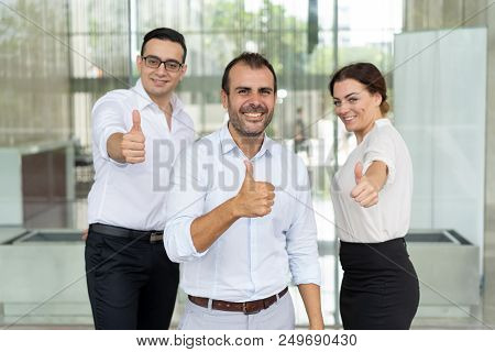 Portrait Of Successful Business Team Showing Thumbs Up. Mid Adult Businessmen And Woman In Office We