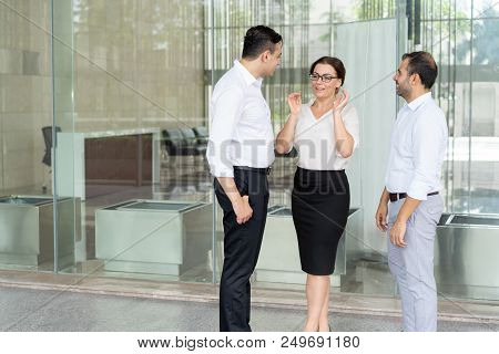 Smiling Female Executive In Glasses Talking To Male Colleagues. Three Business Partners Standing At