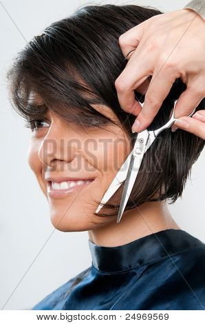 Beautiful happy young woman cutting hair at the hairdresser salon poster