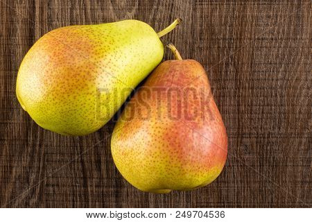 Group of two whole fresh red pear forelle variety flatlay on brown wood poster