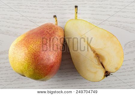 Group of one whole one half of fresh red pear forelle variety flatlay on grey wood poster