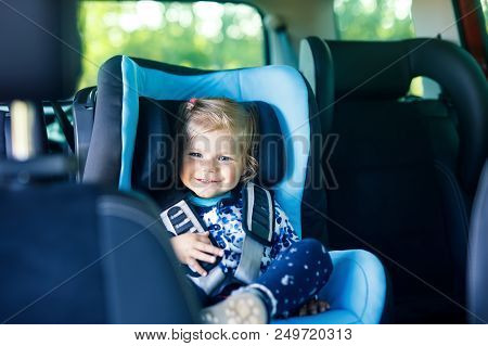 Adorable Baby Girl With Blue Eyes Sitting In Car Safety Seat. Toddler Child Going On Family Vacation