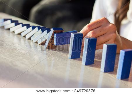 Close Up Of Businessman Hand Stopping Falling Wooden Dominoes Effect From Continuous Toppled Or Risk