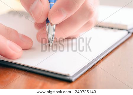 A Macro Of A Male Hand Writing In A Blank Organizer With A Biro