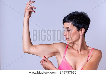 Calm young adult female pinching and stretching skin on tricep portion of bent arm poster