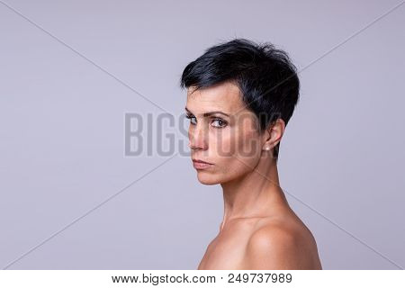 Suspicious Woman Looking Sideways At The Camera With A Serious Thoughtful Expression Isolated On Gre