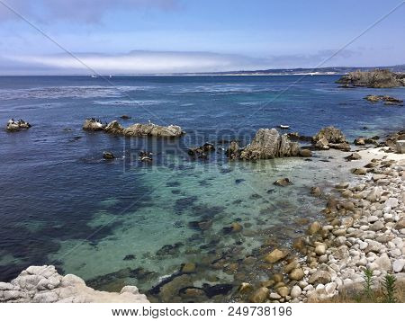The Rocky Coastline Along Pacific Grove, California With The Blue And Teal Waters Of Monterey Bay