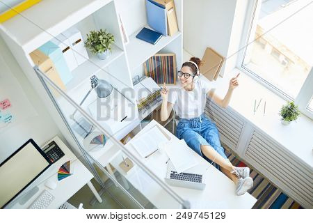 Happy female in casualwear listening music in headphones and dancing by desk with her legs on its top