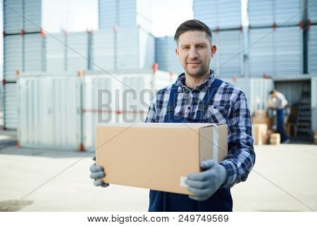 Content handsome manual worker in workwear holding cardboard box and looking at camera while working at container storage area