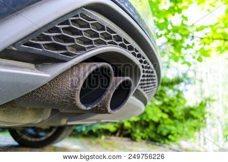 Close Up Of A Car Dual Exhaust Pipe. Double Exhaust Pipes Of A Modern Sports Car. Car Exterior Detai