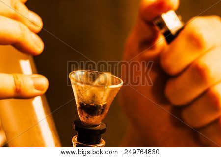 bong and a lighter in his hands. A man smokes cannabis weed, Smoke on a black background. Concepts of medical marijuana use and legalization of the cannabis. On a black background poster