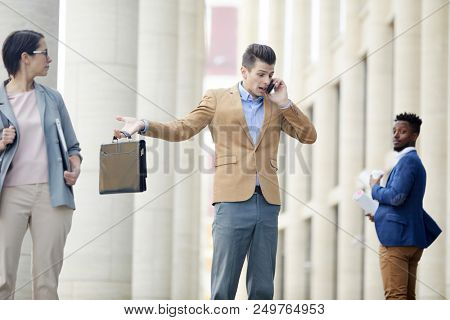 Puzzled confused young businessman talking on phone loudly and shrugging shoulders in despair while standing on city street, business people looking at him while walking