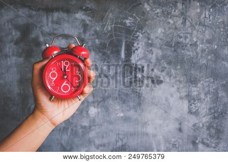 Hand Of Businessman Hold An Alarm Clock Showing Almost 12 O Clock, On Modern Loft Cement Wall Backgr
