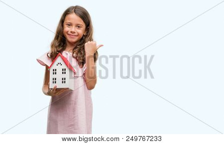 Brunette hispanic girl holding little house pointing and showing with thumb up to the side with happy face smiling