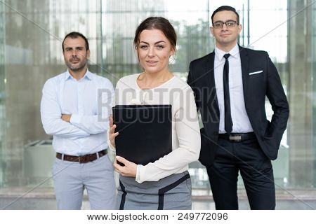 Attractive Smiling Business Woman With Folder And Two Partners In Background. Positive Ambitious Fem
