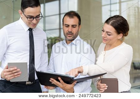 Business Woman Pointing At Document In Hands Of Coworker. Group Of Business People Reading Report Wi