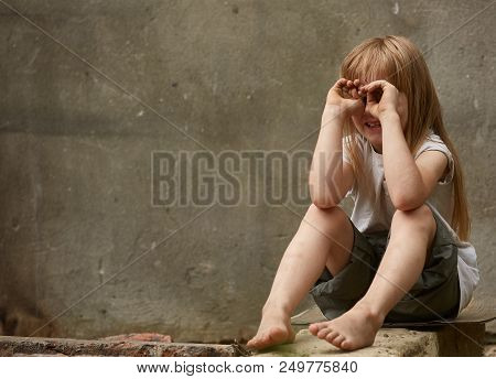 Portrait Of Crying Blond Girl Orphan With Long Matted Hair And Holen Knees Under The Dirty City Wall