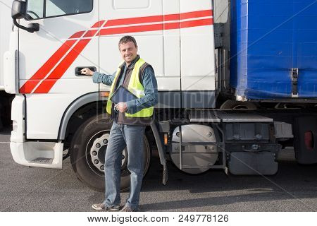 Male Driver Near Big Modern Truck Outdoors Standing In Front Of The Cabin And Trailer