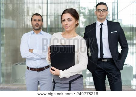 Successful Pretty Business Lady And Her Employees Standing Behind. Positive Female Team Leader Stand
