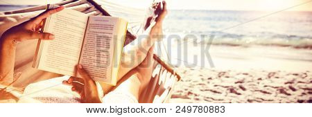 Brunette reading book while relaxing on hammock at the beach