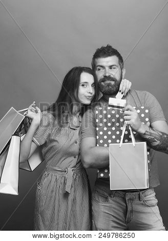 Guy With Beard And Pretty Lady Do Shopping. Bearded Man With Happy Face Holds Credit Cards. Shopping