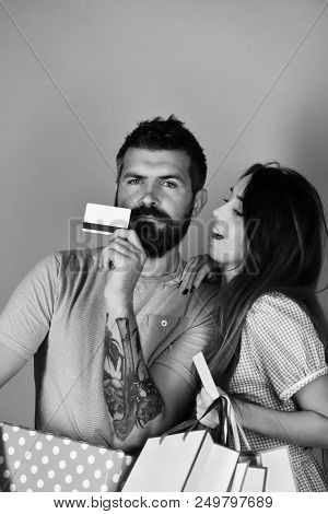 Money And Shopping Concept. Man With Beard Holds Credit Card And Polka Dotted Box. Guy With Beard An