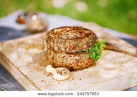 lamb burgers spiced by mint and lamb rub on wooded board