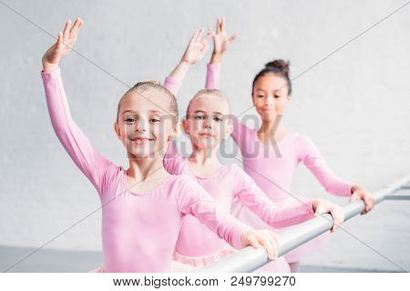 Adorable Multiethnic Kids Practicing Ballet And Smiling At Camera In Ballet Studio