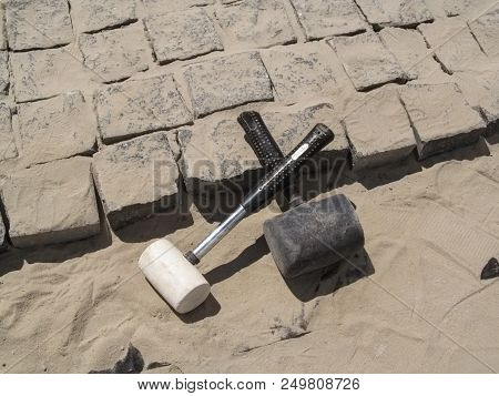 Two crossed rubber hammers lie on the unfinished laying of granite paving stones. Building background - the concept of laying paving slabs and pavers poster