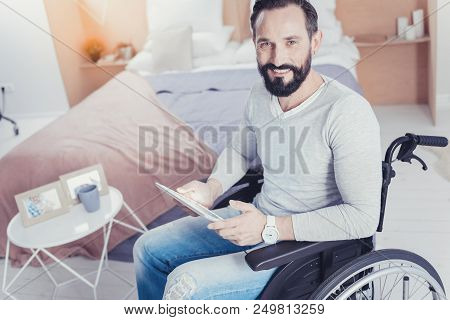Ambitious Man. Clever Ambitious Disabled Person Sitting With A Tablet In His Hands And Looking For A