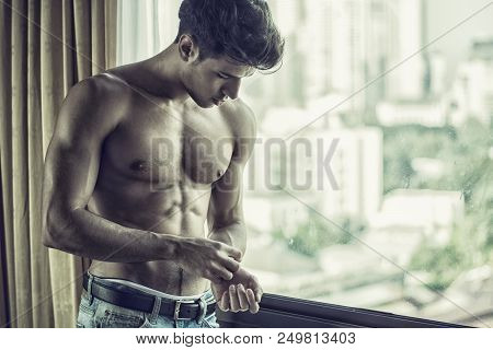 Sexy Handsome Young Man Standing Shirtless In His Bedroom Next To Window Curtains, Adjusting Wrist W