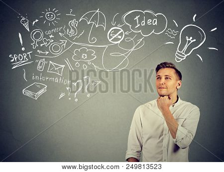 Smart inspired man looking away while making business plan and thinking on new idea against gray background poster