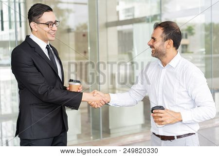 Portrait Of Happy Male Business Colleagues Shaking Hands. Young Manager In Glasses Greeting Mid Adul