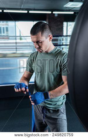 Dark-haired sportsman. Dark-haired handsome promising sportsman standing near punching bag poster