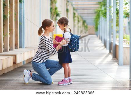 First Day At School. Mother Leads A Little Child School Girl In First Grade