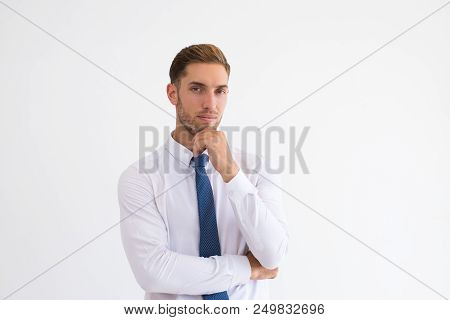 Pensive Business Man Touching Chin And Looking At Camera. Handsome Guy Thinking. Contemplation Conce