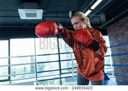 Sport Activity. Blonde-haired Woman Enjoying Sport Activity Greatly While Boxing Actively In Gym