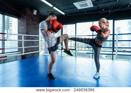 Husband And Wife. Dark-haired Strong Athletic Man Working Out On Boxing Ring With His Appealing Wife