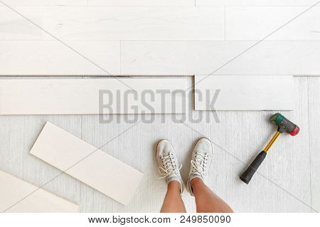 Home improvement floor installation - Worker installing new hardwood flooring at house or condo .Engineered wood floor planks of natural white maple wood. Flooring glued or floating over membrane.
