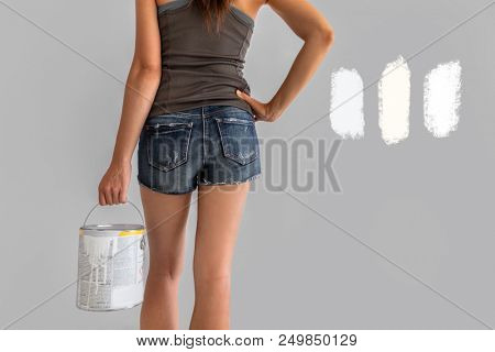 Home renovation woman confused between different shades of white paint choosing tones of warm and cold whites in eggshell sheen. Girl painting walls during house remodel.