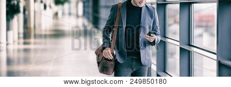Business man texting on mobile phone commuting walking in airport with messenger bag using cellphone texting sms message on smartphone app - young businessman commute lifestyle panoramic banner.