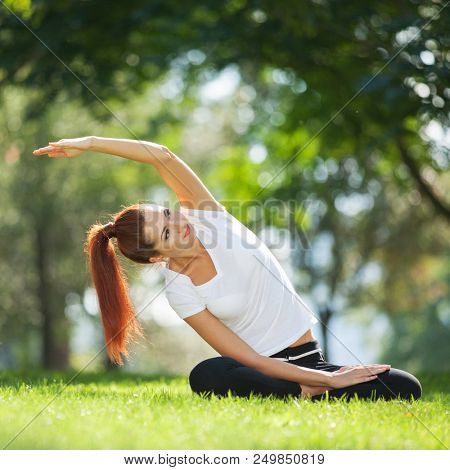 Yoga outdoor. Happy woman doing yoga exercises, meditate in the park. Yoga meditation in nature. Concept of healthy lifestyle and relaxation. Pretty woman practicing yoga on the grass