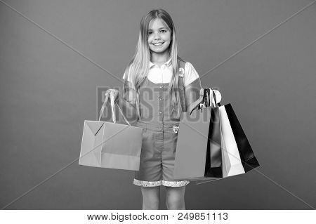 Happy Child With Shopping Bags On Violet Background. Little Girl Smile With Paper Bags. Kid Shopper