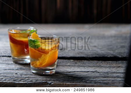 Peach Tea With Pieces Of Fruit And Mint On A Wooden Background, Selective Focus