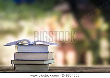 Open Vintage Book On Stack Books On Table With Blurred Green Nature Background. Back To School Conce