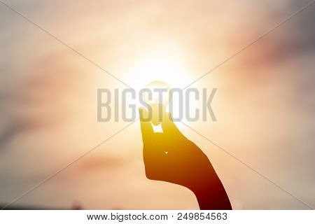 Idea And Creativity Concept. Silhouette Hand Holding Light Bulb With Solar Energy. New Ideas Innovat