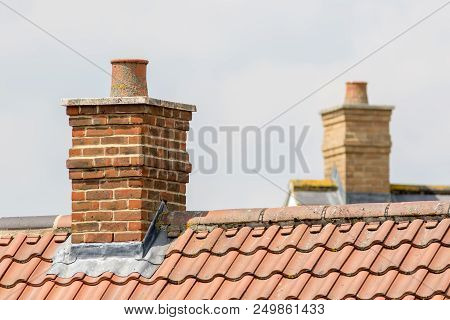 Brick Chimney Stack On Modern Contemporary House Roof Top. Urban Housing Estate Tiled Roof In Close-