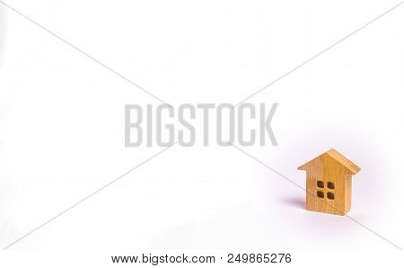 A Small Wooden House Stands On A White Background. The Concept Of Buying And Selling Real Estate, Re