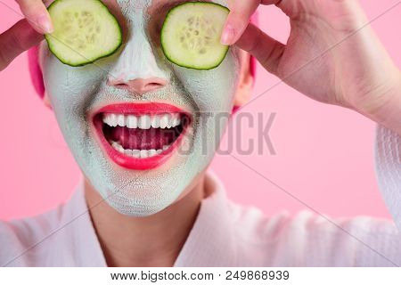 Close Up Portrait Of Woman With Facial Cosmetical Mask And Cucumber Slice On Eyes. Cosmetic Procedur